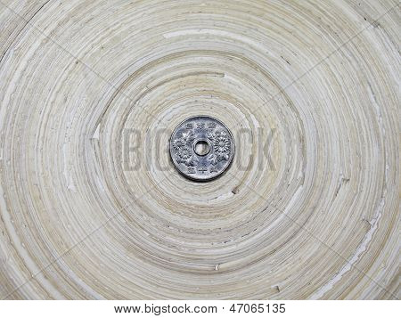 Japanese Fifty Yen Coin on Bamboo Circular Tray