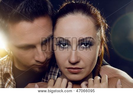 Couple Of Lovers. The Guy Holding The Girl's Neck, Hugging Her Tightly, Looking At Her. The Girl Wit