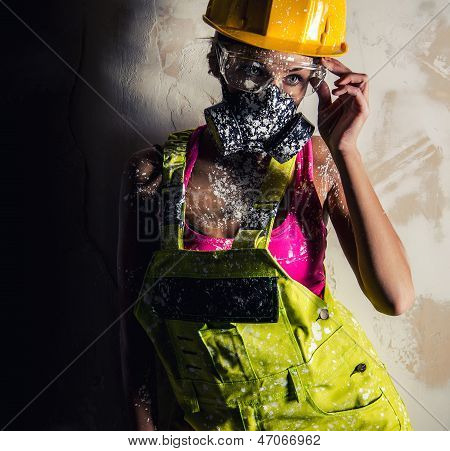Female Construction Worker Wearing Coverall, Hardhat And Respirator Posing Over Obsolete Wall