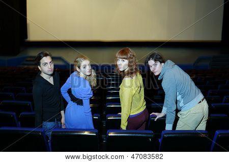 Quatro jovens amigos sentar nos assentos no hall do teatro cinema e olhem para trás.