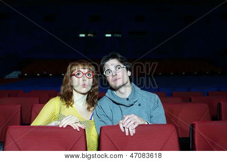Young man and woman in glasses watch movie and surprise in cinema theater.