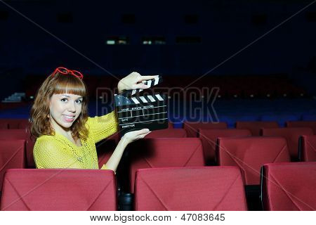 Happy beautiful woman shows clap board in auditorium of movie theater.