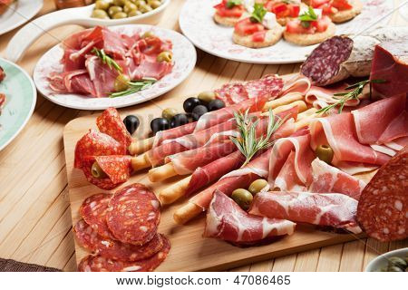 Italian prosciutto, cured pork meat on cutting board