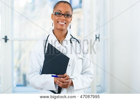 Young female black doctor standing at a window in clinic with a file or dossier