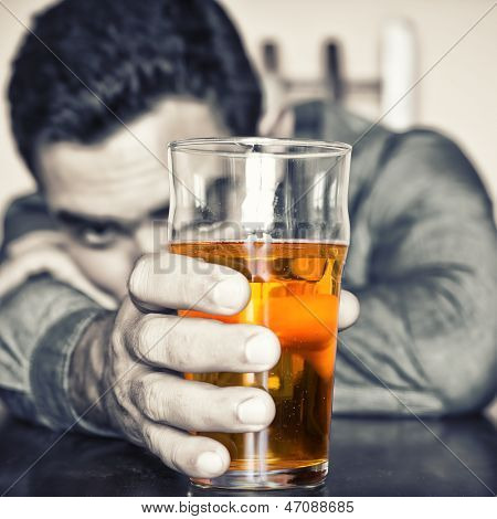 Deamatic image of a drunk man holding a glass of beer