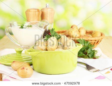 Concursos jovens batatas com creme de leite e ervas na panela na mesa de madeira no fundo natural