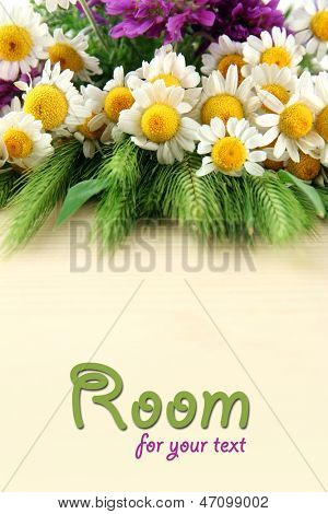 Wild flowers and green spikelets on wooden table with copy space