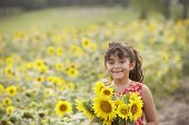 stock photo of tooth gap  - Young girl holding sunflowers - JPG