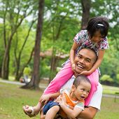 Southeast Asian family having fun at green outdoor park. Beautiful Muslim family playing together.