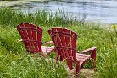 image of bull rushes  - Red plastic Adirondack chairs placed for a view of the river - JPG
