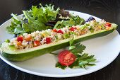 stock photo of quinoa  - Zucchini stuffed with quinoa and vegetables on a white plate - JPG