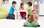 stock photo of shy girl  - Sad girl feeling excluded from the group of playing kids - JPG