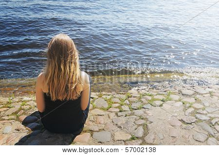 Young Girl Sits By The Water
