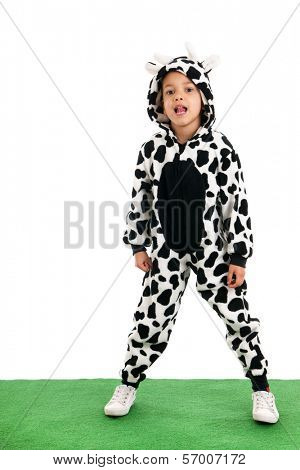 Little boy dressed as cow sitting in the grass