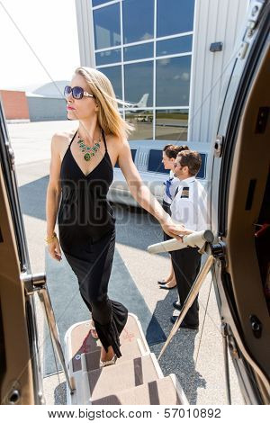 Elegant woman in dress boarding private jet with pilot and airhostess standing by at airport terminal