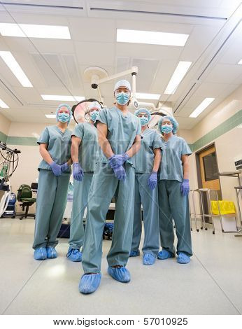 Low angle portrait of medical team in scrubs standing inside operation room