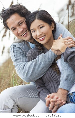 Young Asian Chinese man & woman, boy & girl, couple sitting in the sand dunes on a beach