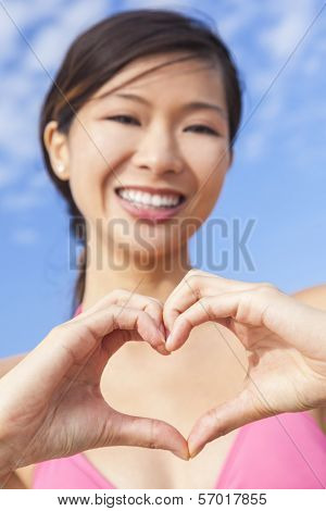 Beautiful happy young Chinese Asian woman or girl in a pink bikini making a heart shape symbol with her hands