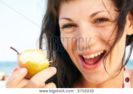 Woman Eats Fruit On The Beach