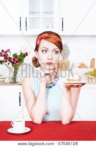 Sad beautiful young woman looking on cake