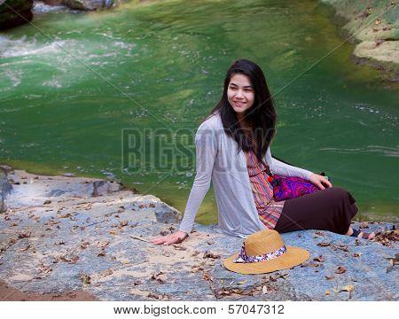 Beautiful biracial teen girl sitting by river