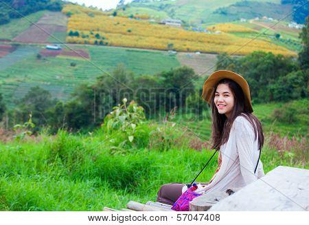 Teen Girl Sitting On Hillside Of Thailand