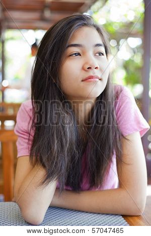 Teen Girl Sitting At Table, Thinking