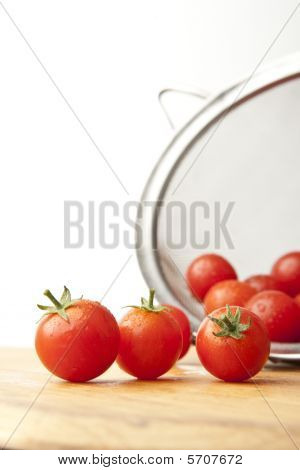 Washed Tomatoes In Colander On Cutting Board