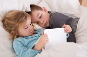 stock photo of pyjama  - Cute little girl and boy reading a bedtime story as they lie together in bed looking at a tablet computer as they prepare to go to sleep with the little sister holding the notebook - JPG