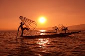 foto of catching fish  - Silhouette of traditional fishermans in wooden boat using a coop - JPG