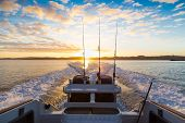 stock photo of fishing rod  - Looking behind a speeding boat in the early morning watching the sunrise on Waiheke island New Zealand - JPG