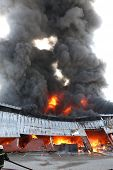 stock photo of fireman  - Warehouse building burning with intense flames and fireman attending - JPG