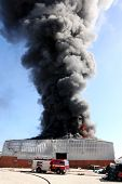 picture of fireman  - Warehouse building burning with intense flames and fireman attending - JPG