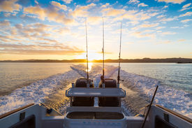 foto of outboard  - Looking behind a speeding boat in the early morning watching the sunrise on Waiheke island New Zealand - JPG