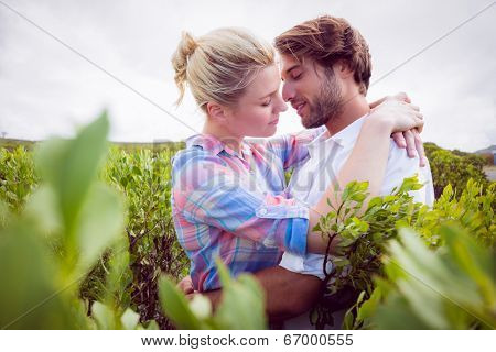 Smiling couple embracing outside among the bushes on a sunny day