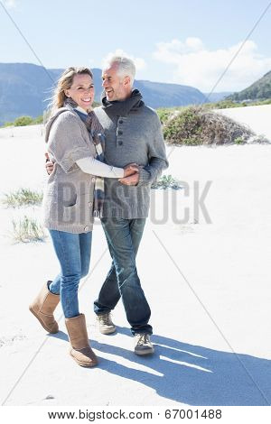 Smiling couple strolling on the beach in warm clothing on a bright but cool day