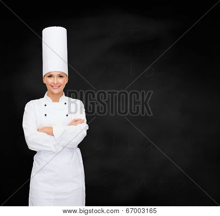 cooking and food concept - smiling female chef with crossed arms