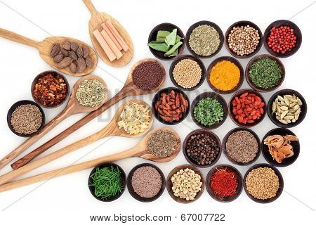 Large herb and spice sampler in a selection of wooden bowls and spoons over white background.
