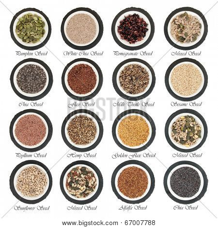 Large seed super food selection in  porcelain bowls over slate rounds and white isolated background with titles.