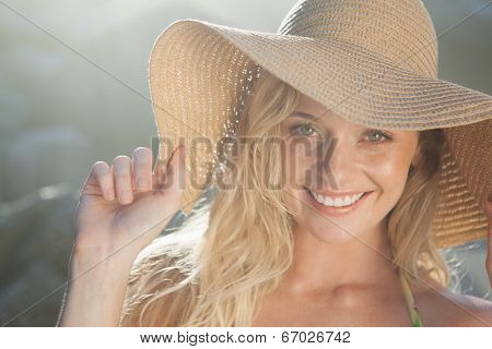 Gorgeous blonde in straw hat smiling at camera on beach on a sunny day