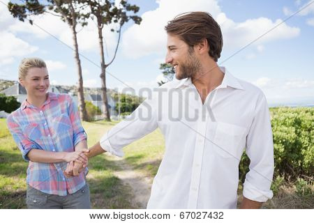 Smiling couple standing outside together in their garden on a sunny day