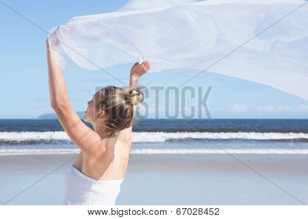Pretty blonde holding up white shawl on the beach on a bright day
