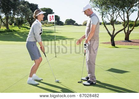 Lady golfer on the putting green at the eighteenth hole with partner on a sunny day at the golf course