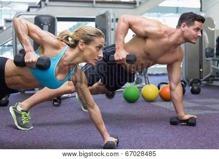 Bodybuilding man and woman holding dumbbells in plank position at the gym