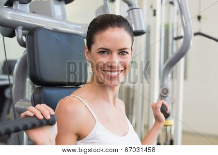 Fit brunette using weights machine for arms smiling at camera at the gym