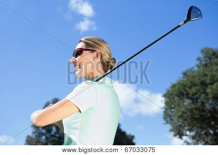 Female golfer standing holding her club smiling on a sunny day at the golf course