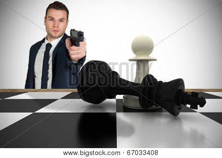 Composite image of serious businessman pointing a gun at chess piece against white background with vignette