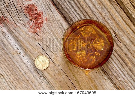 Glass Of Whiskey And A Coin On A Bar Counter
