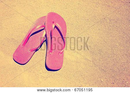 summer vacation background with a pair of sandals on a sandy beach done with a retro vintage instagram filter
