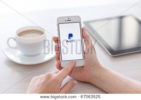 Female Hands Holding White Iphone 5S With App Paypal On The Screen  In The Office